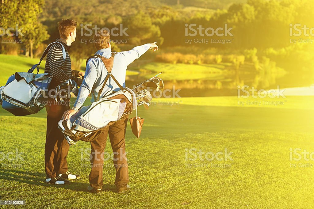 Two young male golfers pause on idyllic golf course stock photo