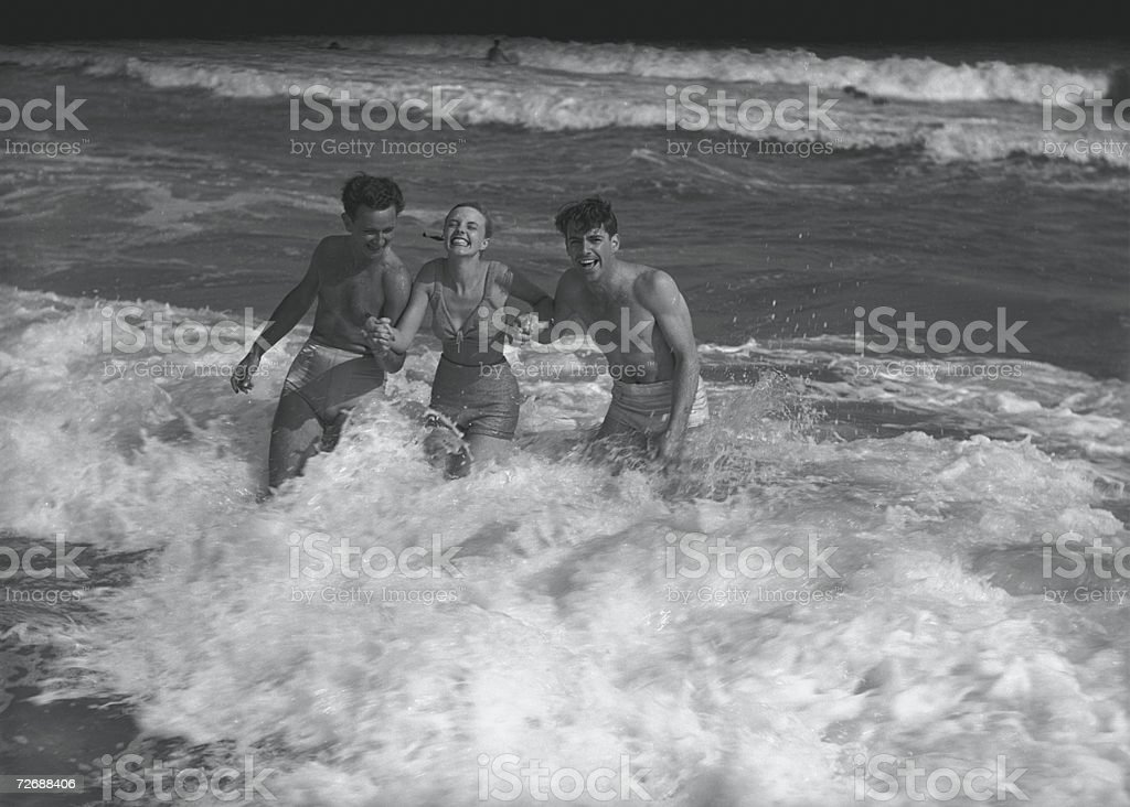 Two young man and woman playing in wave, (B&W) stock photo