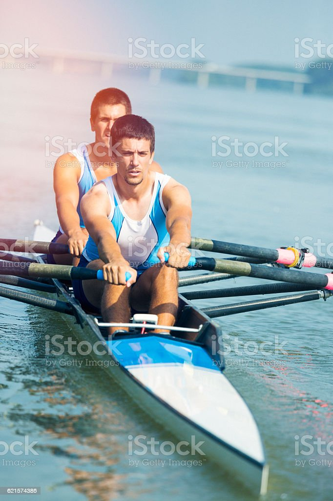Two young man rowing on the river stock photo