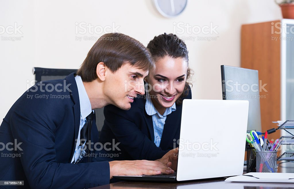 Two young managers using laptop at work stock photo