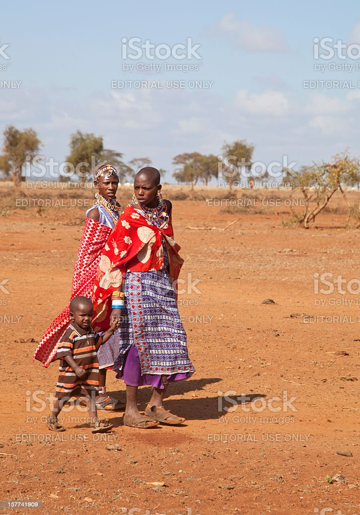 Two young masai women in traditional dress with a child. stock photo