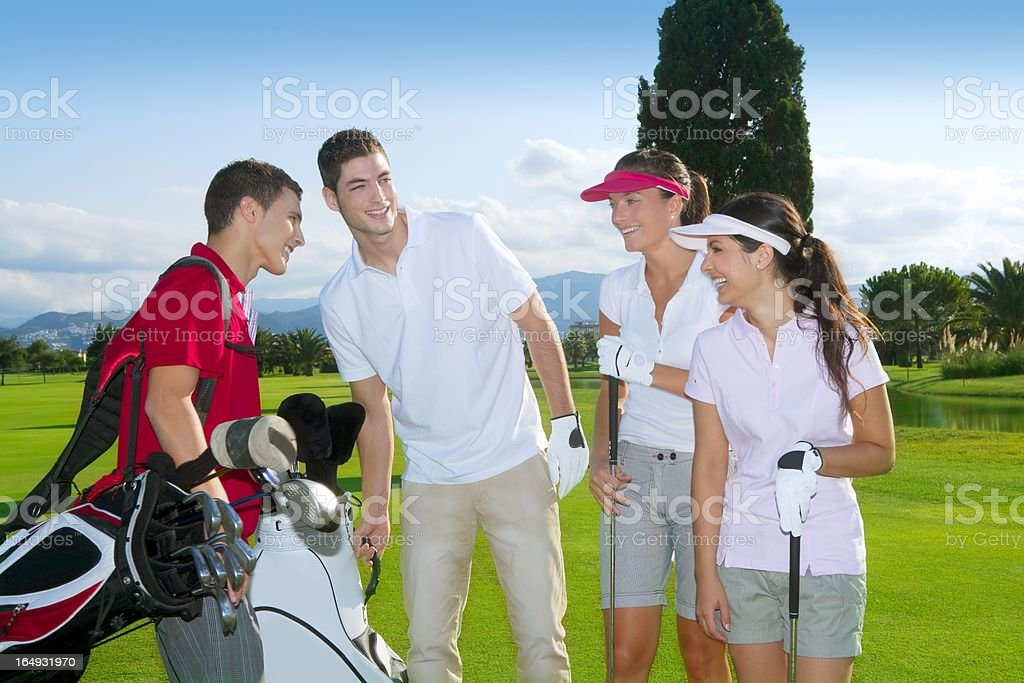 Two young men and two young women on a golf course stock photo