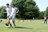 Two Young Men Compete In Three-Legged Race At Summer Fundraiser