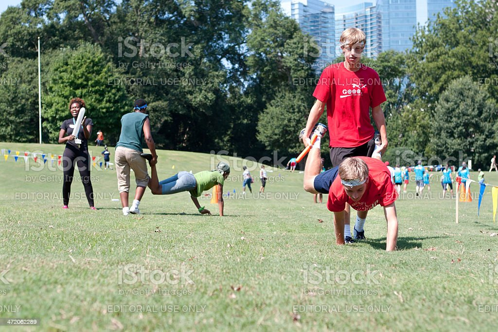 Two Young Men Compete In Wheelbarrow Race At Summer Fundraiser stock photo