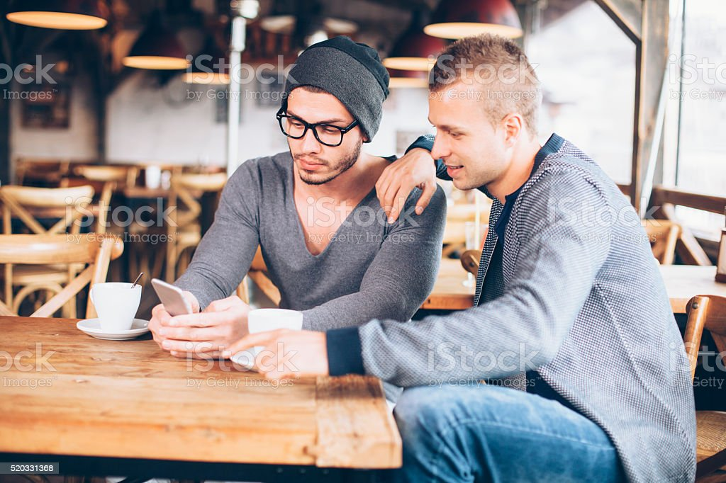 Two young men drinking coffee in a bar stock photo