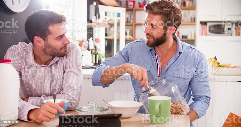 Two Young Men Eating Breakfast In Kitchen Together stock photo