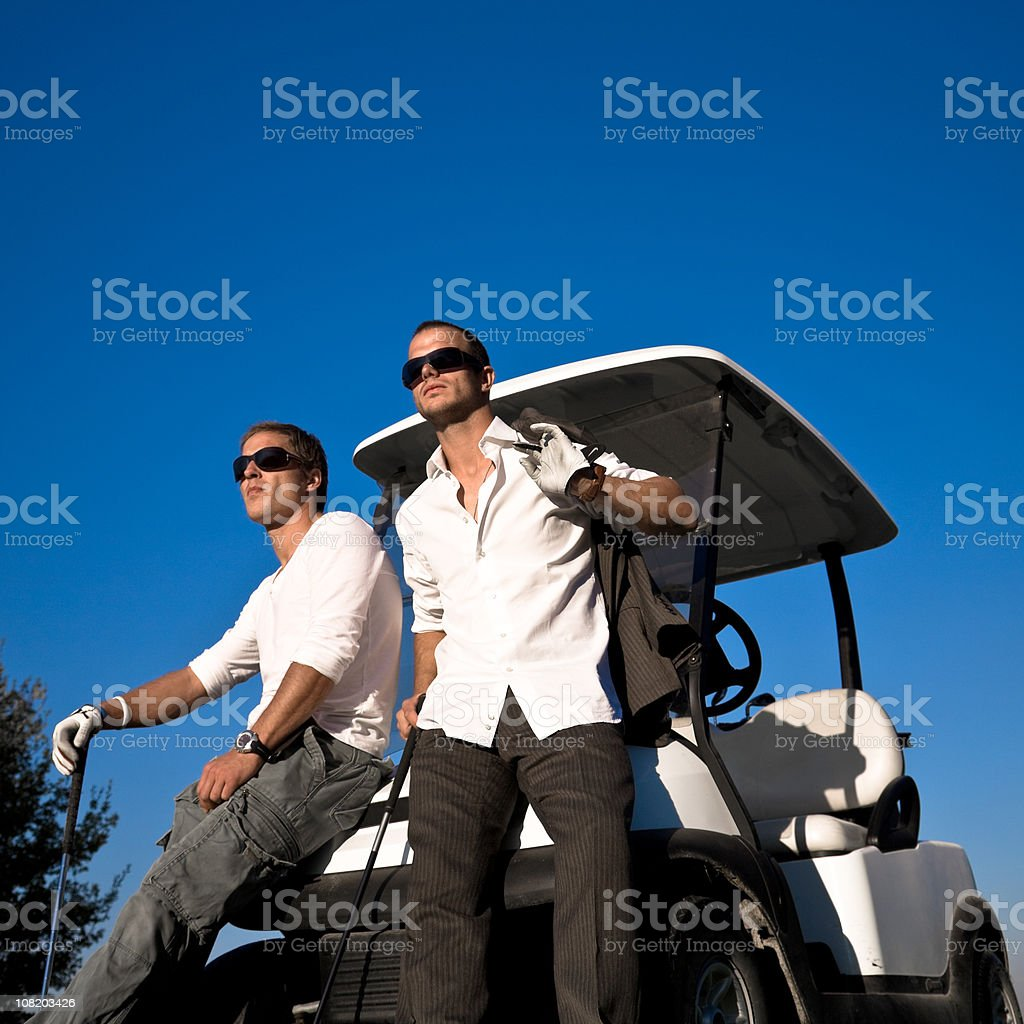 Two Young Men Golfers Relaxing on Golf Cart royalty-free stock photo