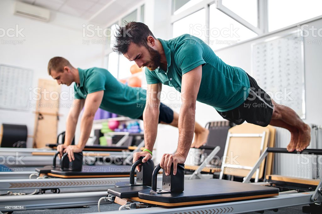Two young men having a Pilates class at health club. stock photo