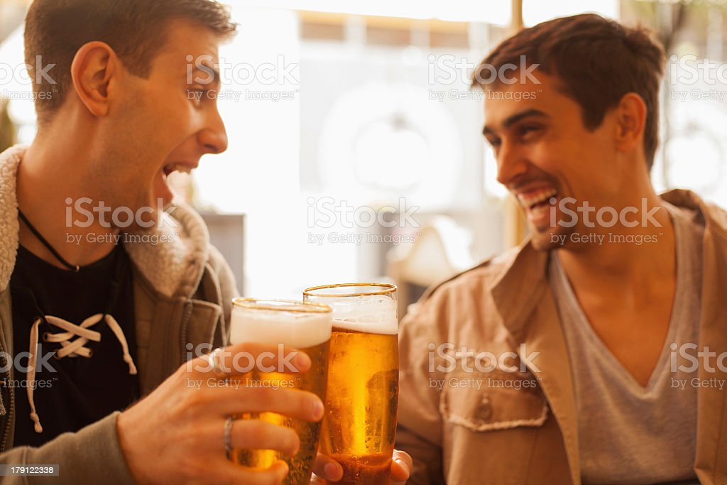 Two young men laughing and drinking beer together  royalty-free stock photo