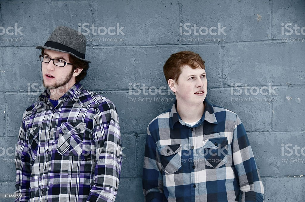Two young men leaning on a wall royalty-free stock photo