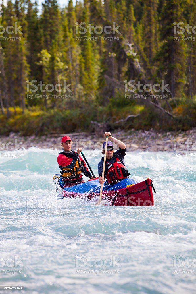 Two young men paddle a river in Northern Canada stock photo