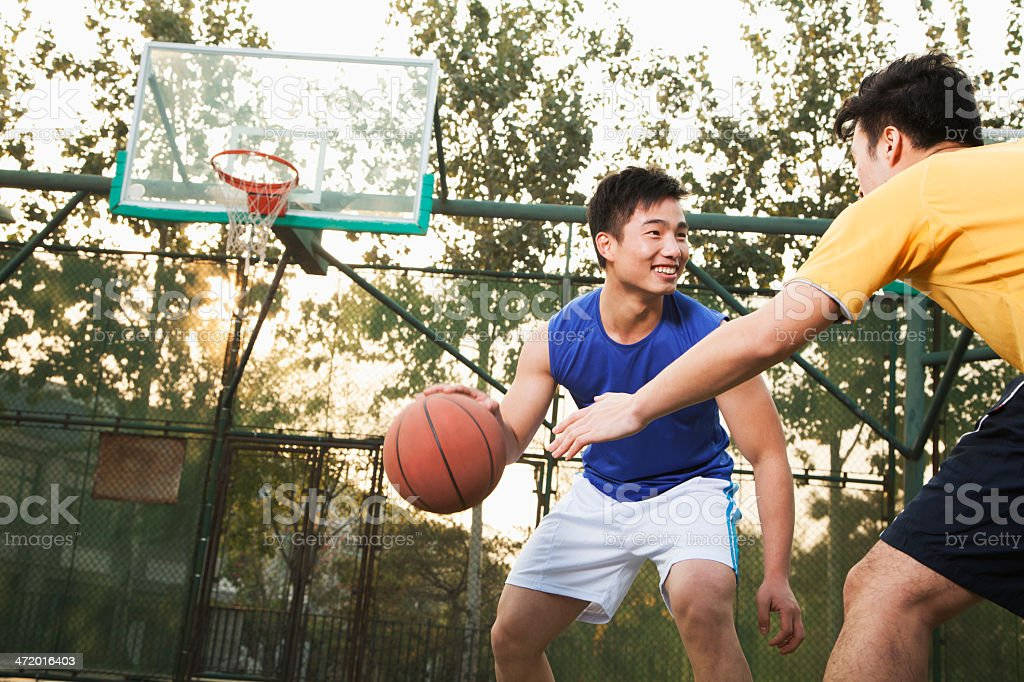 Two young men playing basketball on a public outdoor court stock photo