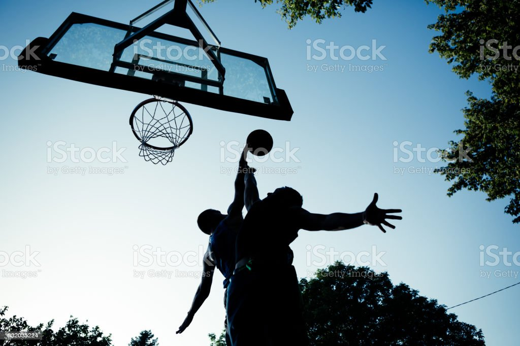 Two young men playing basketball on outdoor court stock photo