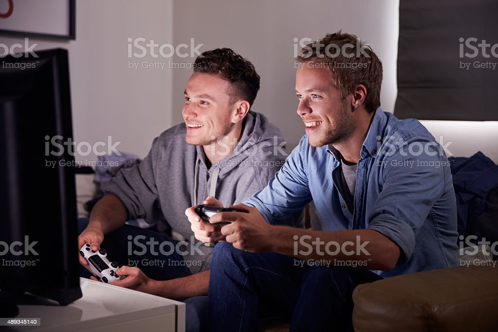 Two Young Men Playing Video Game At Home stock photo