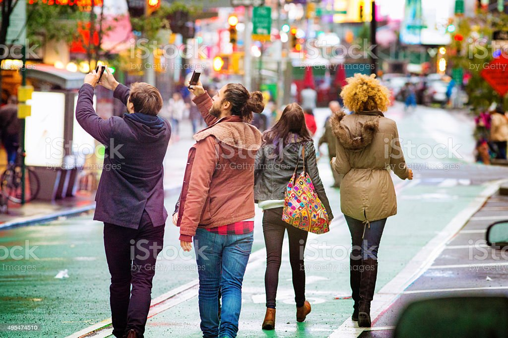 Two young men snapping pictures with mobile phones on Broadway stock photo