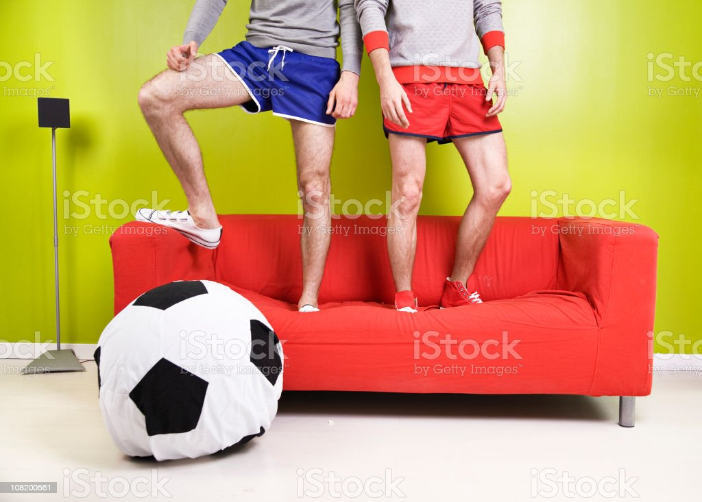 Two Young Men Standing on Couch with Soccer Ball Pillow royalty-free stock photo