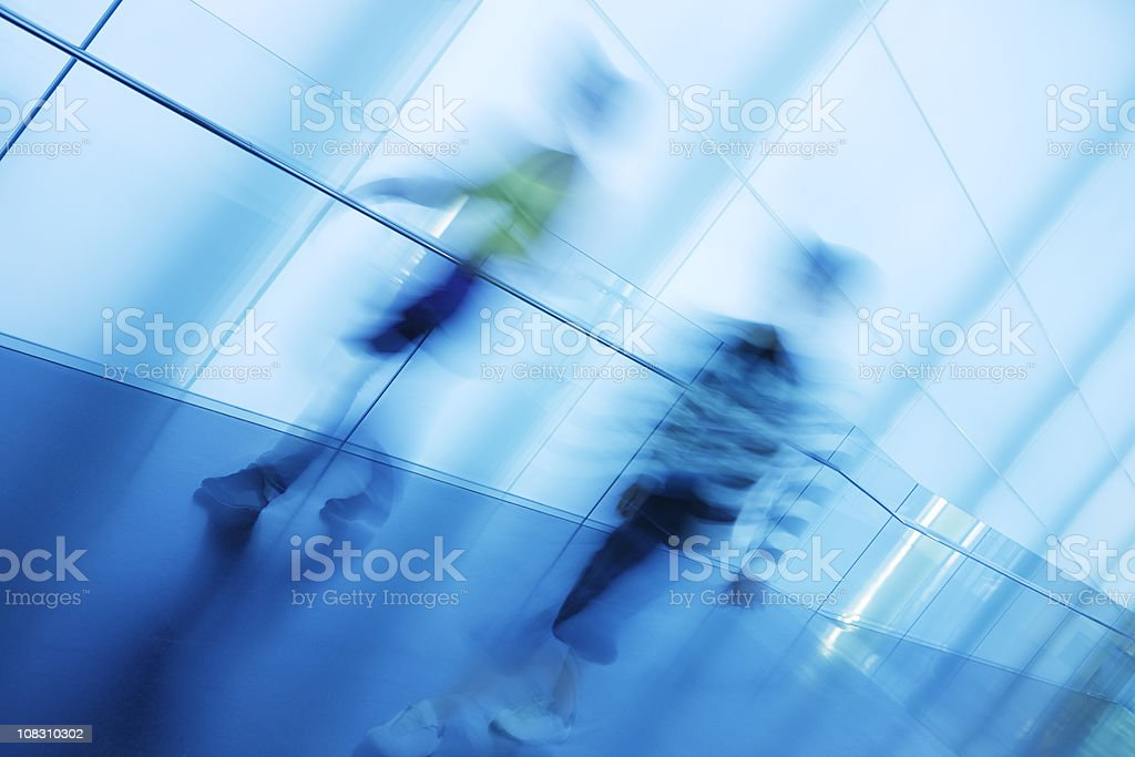 Two Young Men Walking Down Modern Corridor, Blurred Motion royalty-free stock photo