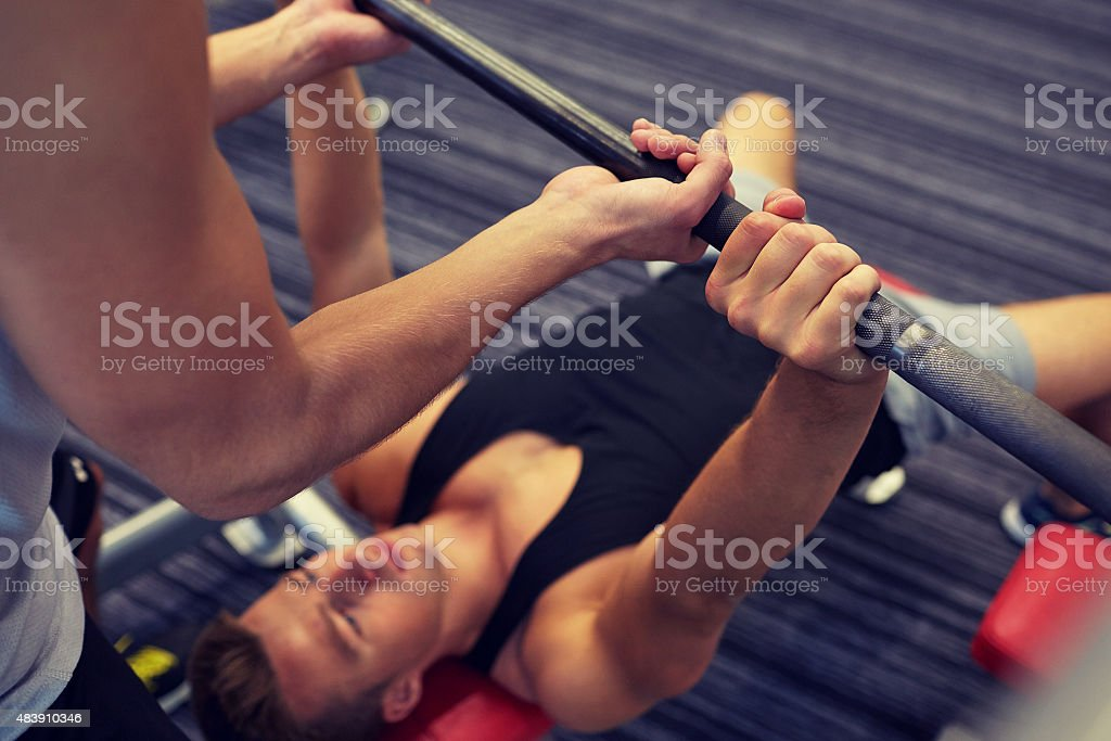 two young men with barbell flexing muscles in gym stock photo