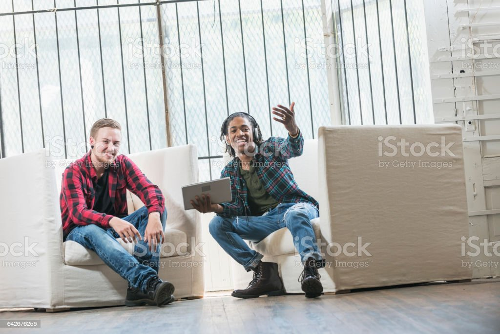 Two young men with tablet, waving someone to join them stock photo