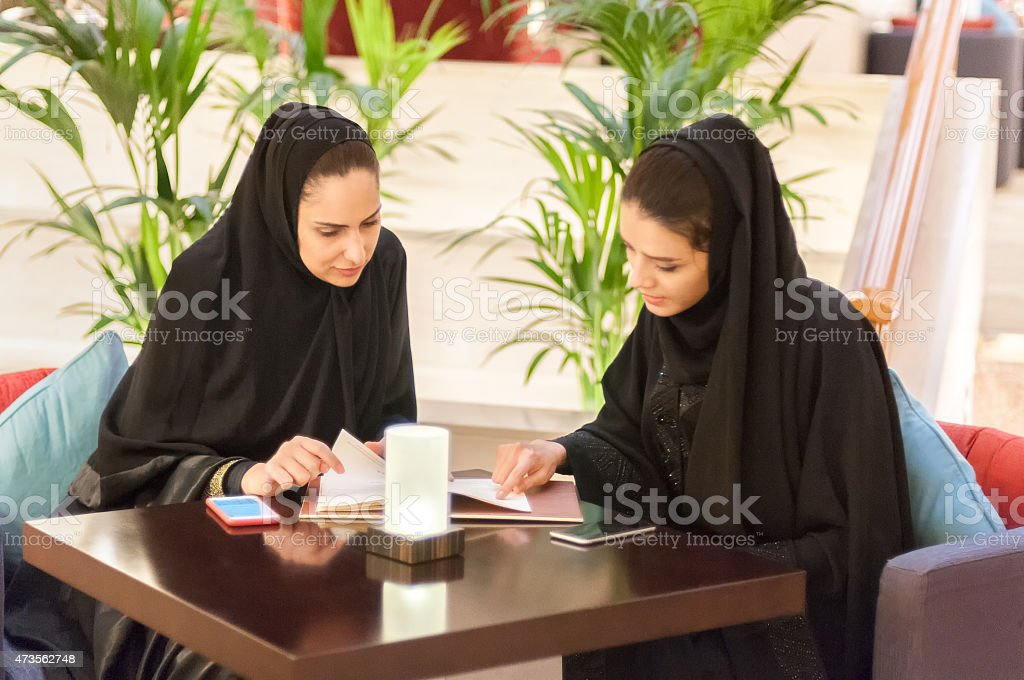 Two Young Middle Eastern Women Looking at Menu in Caf? stock photo