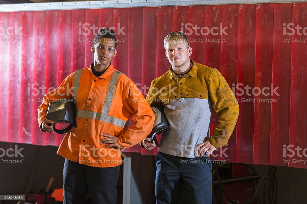 Two young multi-ethnic workers with welding masks stock photo