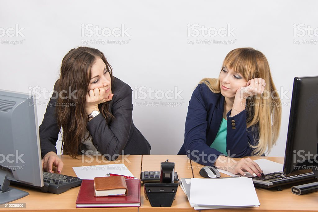 Two young office employee wearily looking at each stock photo
