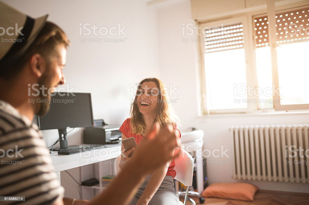 Two young people laughing at the office stock photo