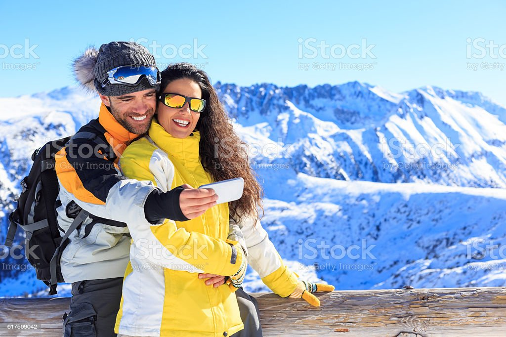 Two young people making selfie on top mountain stock photo