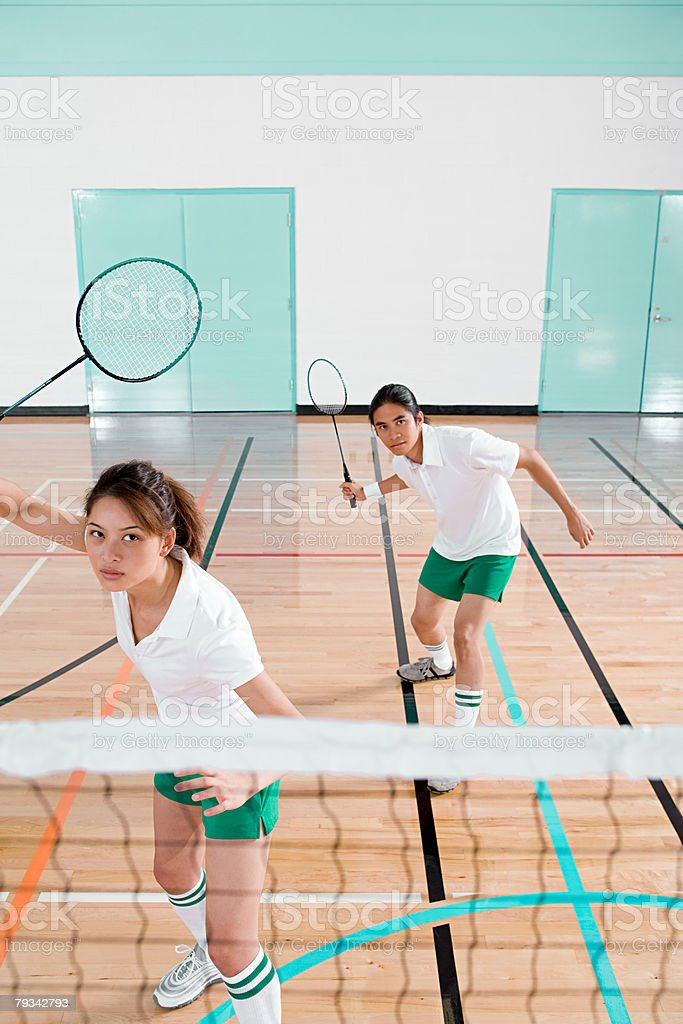 Two young people playing badminton stock photo