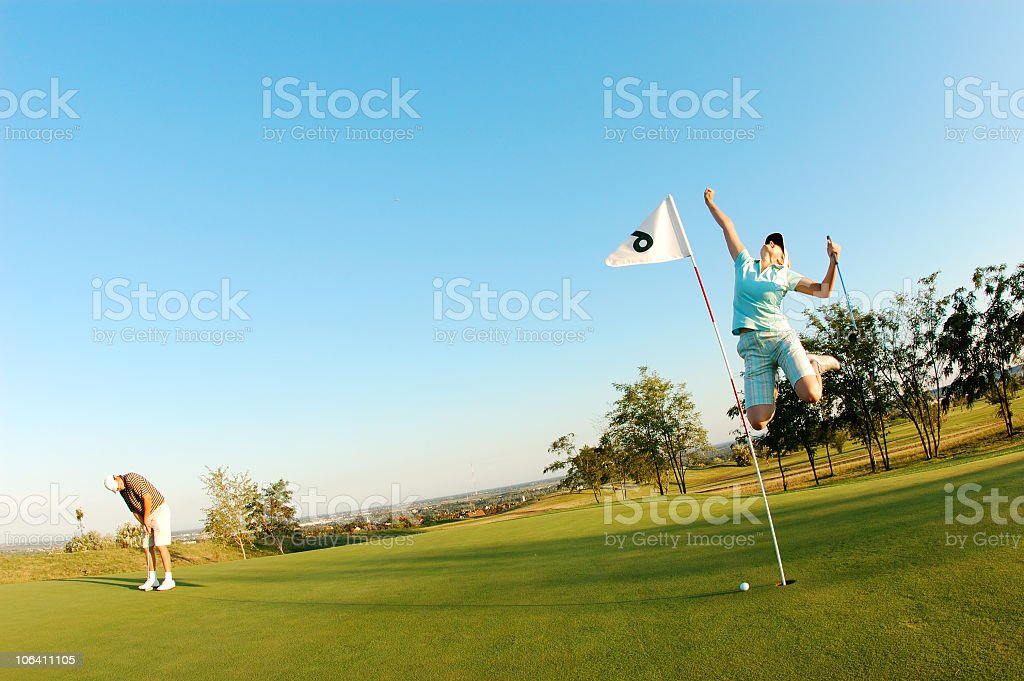 Two young people playing golf royalty-free stock photo