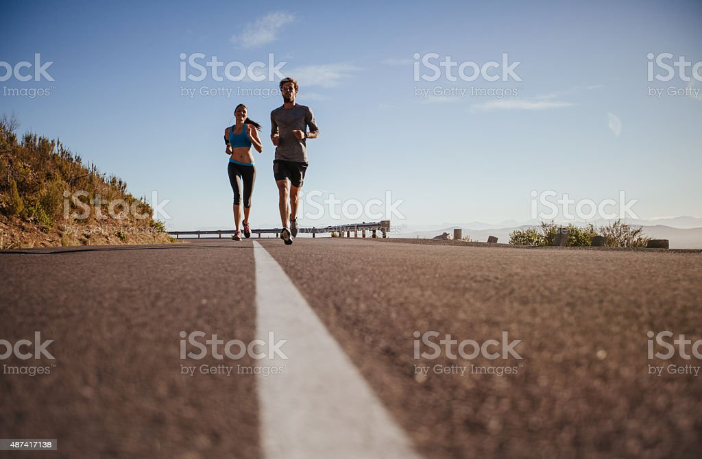 Two young people running on country road stock photo