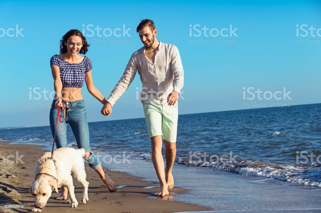 two young people running on the beach kissing and holding tight with...