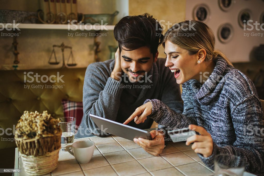 Two young people shopping online using digital tablet stock photo
