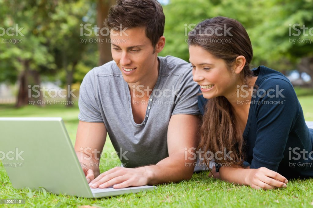 Two young people using a laptop while lying royalty-free stock photo
