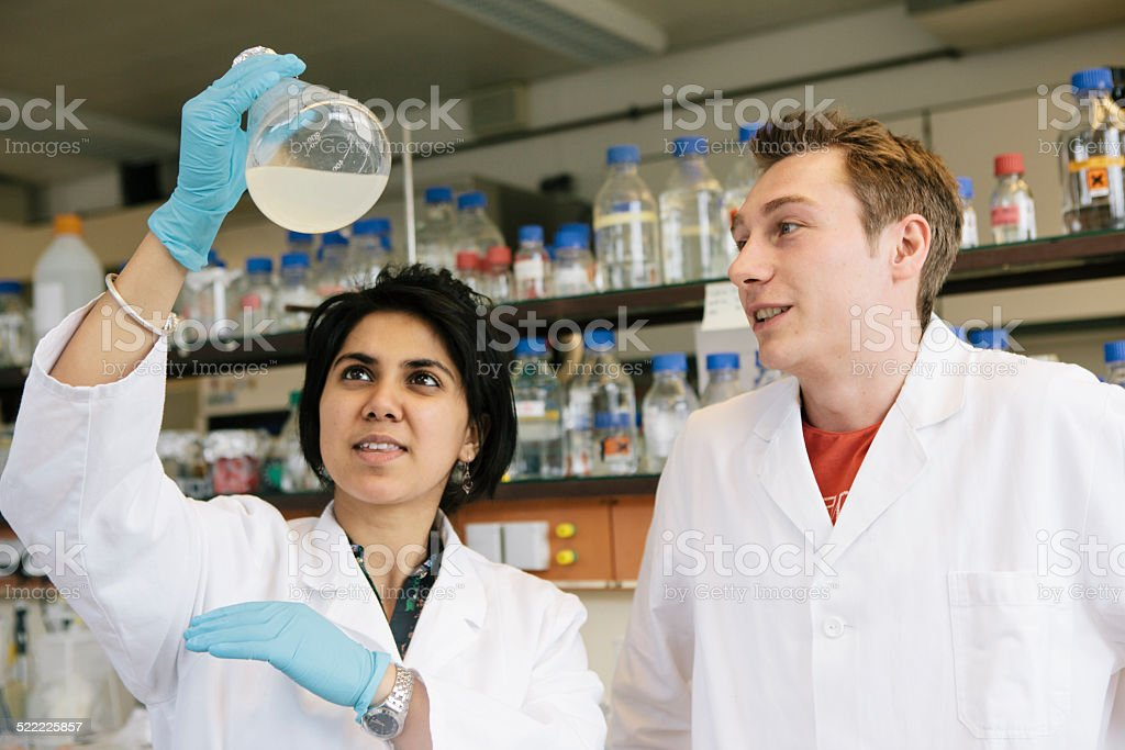 two young researchers analyse the liquid in a flask stock photo