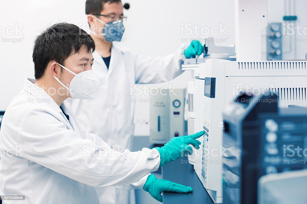 Two young researchers carrying out experiments in a lab stock photo