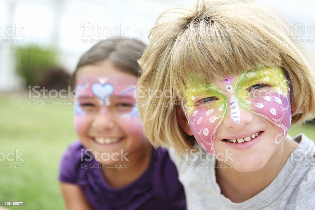 Two young smiling girls with their faces painted stock photo
