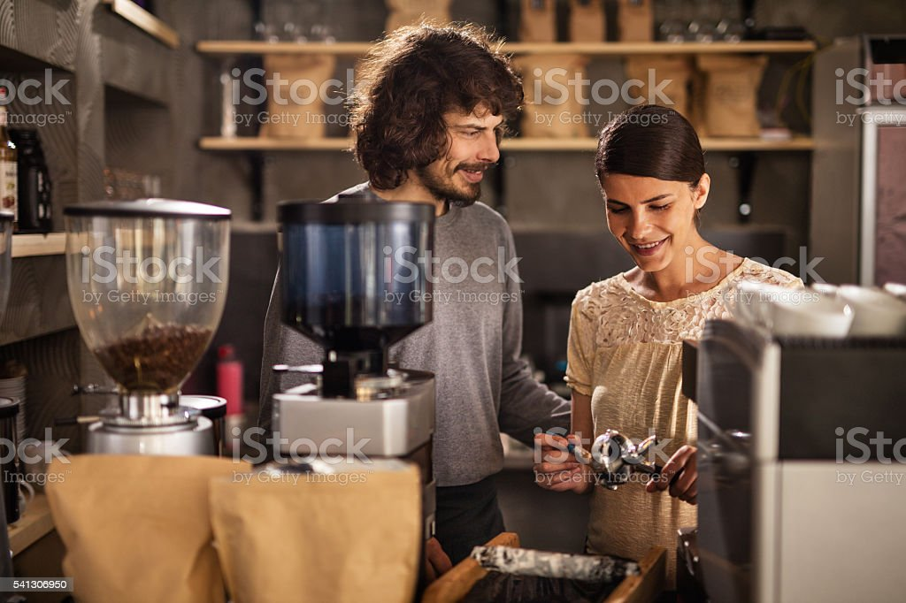 Two young smiling waiters preparing coffee in a cafe. stock photo
