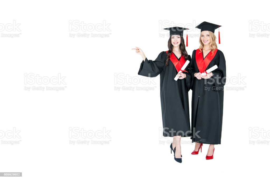 Two young smiling women in mantles and mortarboards holding diplomas and pointing away stock photo