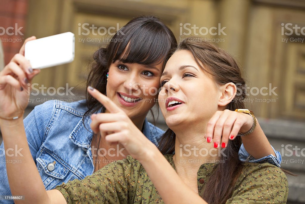 Two Young Smiling Women With Smartphone royalty-free stock photo