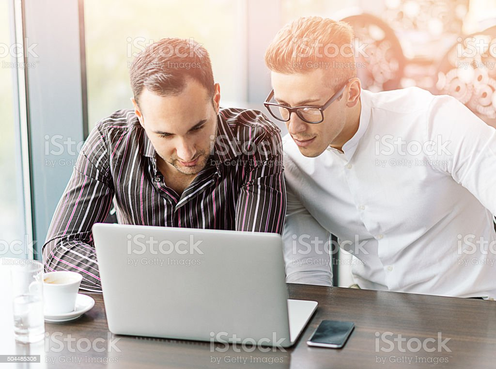 Two young successful businessmen working on laptop in meeting room stock photo