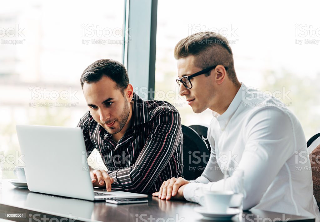 Two young successful businessmen working on laptop in office building stock photo