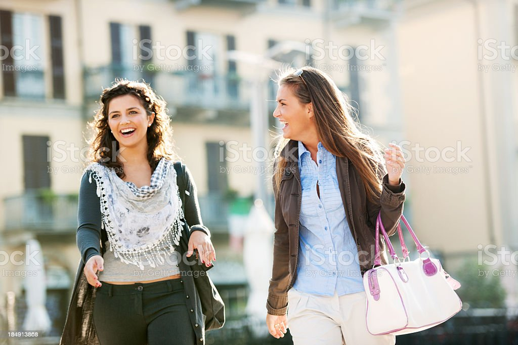 Two young teenagers walking down the streets of a city royalty-free stock photo