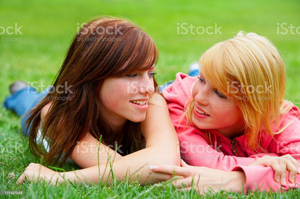 Two young teens relaxing in a park. stock photo