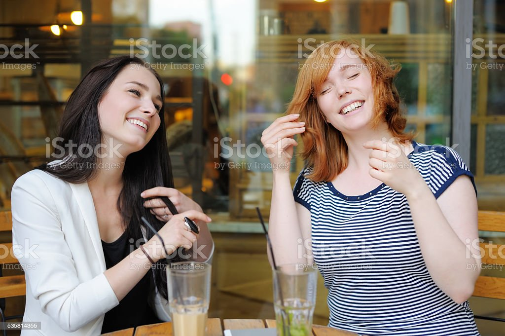 Two young woman at the outdoors cafe stock photo
