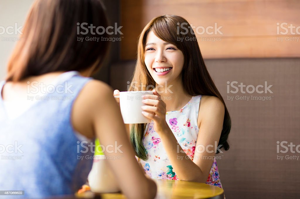 two young woman chatting in a coffee shop stock photo