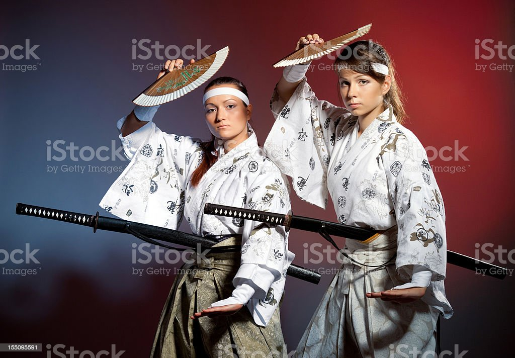 Two young woman in japanese clothes performing a kenbu movement with...