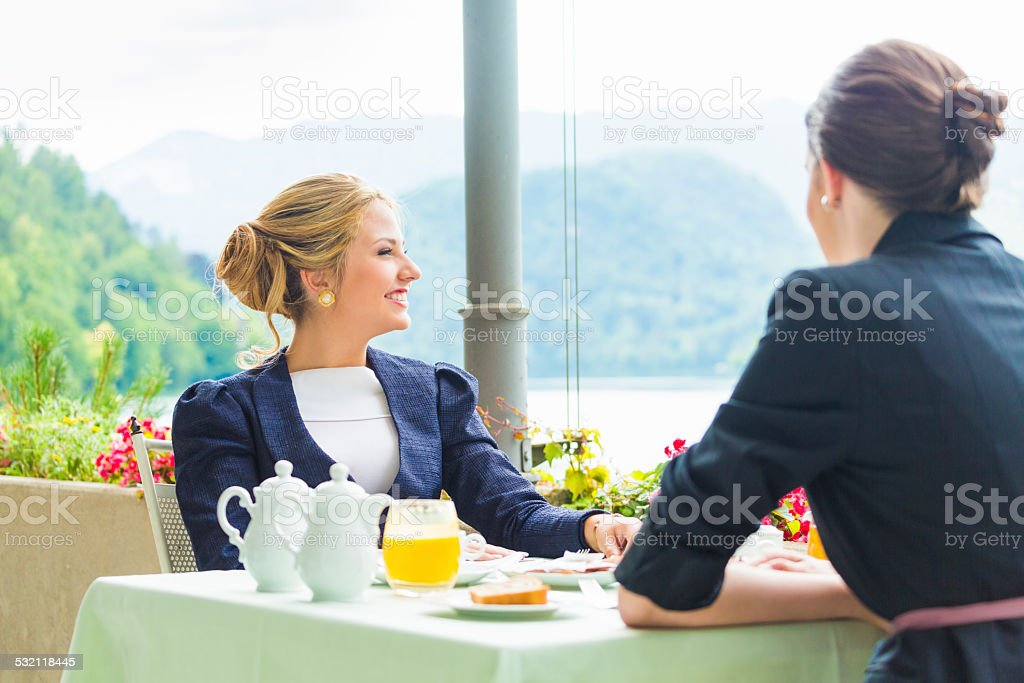 Two young woman having business lunch on restaurant terrace stock photo