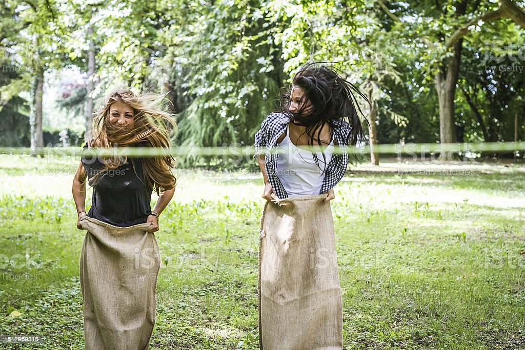 Two young woman having fun playing sack race stock photo