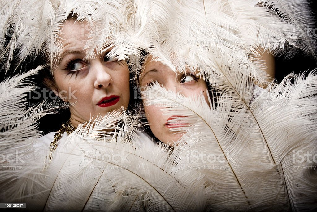 Two Young Woman Posing Behind Feather Fans stock photo